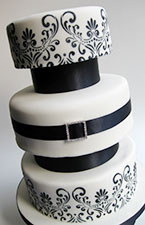 Gluten-free, dairy-free wedding cake. Top tier: Luxury Jamaica Fruit Cake; middle and bottom tiers: Tunisian Orange & Almond Cake and Jamaica Ginger Cake. This wedding cake is gluten free and dairy free. Covered with marzipan and white icing, with stencil design and ribbon to decorate. Delivered in London