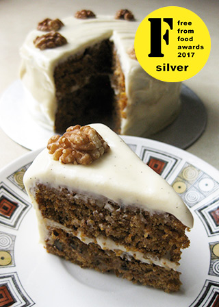 Awarded Silver at the FreeFrom Food Awards 2017, this lush glutenfree vegan carrot cake is made with organic carrot and coconut, crushed pineapple and chopped walnuts, and spiced with cinnamon, Jamaica allspice, ginger and Madagascar vanilla seeds. With creamy soya/vanilla seed frosting. All ingredients gluten-free, egg-free and dairy-free, no animal products