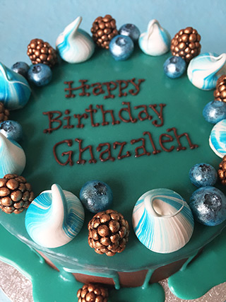 A gluten-free birthday cake, made with chocolate & almonds and covered with dark ganache and turquoise white-choc drizzle. Decorated with meringue kisses and frosted fresh berries. All made with glutenfree ingredients, and delivered in London