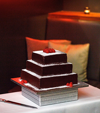 A gorgeous 3-tier gluten free chocolate wedding cake. Reine de Saba (gluten-free Chocolate & Almond Cake with Appleton Jamaica Rum) for all three tiers. Made with organic ingredients. Frosted with organic Fairtrade dark chocolate ganache. All ingredients glutenfree