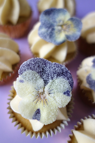 Gluten-free Lemon & Lavender cupcakes made with organic ingredients. Topped with a swirl of buttercream and sugared pansies. All ingredients gluten free. Delivered by hand in London
