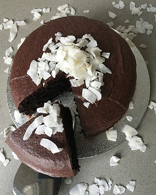A sumptuous dark, rich vegan chocolate cake made with gluten free, dairy free, nut free organic ingredients. Shown with organic coconut chip topping - other toppings available. All ingredients glutenfree, dairyfree, nutfree