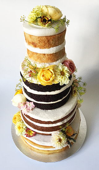 4-tier gluten-free, vegan wedding cake, made with organic ingredients. From the top: Lemon Cake, Dark Chocolate Cake, Carrot Cake, Orange & Almond Cake. All made with gluten free organic ingredients, no animal products. Decorated with organic edible flowers from maddocksfarmorganics.co.uk. Wedding service includes tasting consultation and delivery and assembly at your London venue