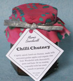 Chilli Chutney: A traditional hand-cut chutney made with untreated garden apples and organic vine fruit, with a little chilli kick that won't blow your head off! Wonderful with ham and game, or tossed with hot roast parsnip or pumpkin. Finished with a fabulous fabric topper tied with silver paper ribbon