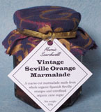 Vintage Seville Orange Marmalade: Coarse cut, made with organic Spanish Sevilles (hand cut), unrefined cane sugar and blackstrap molasses - dark and intense. Once tasted, nothing else comes close: this is the perfect gift for the marmalade connoisseur. Finished with a fabulous fabric topper tied with gold paper ribbon